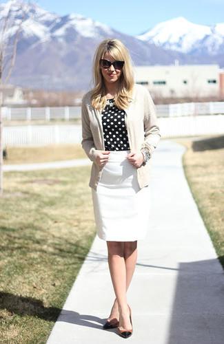 Cómo combinar: cárdigan en beige, blusa de manga larga a lunares en negro y blanco, falda lápiz blanca, zapatos de tacón de cuero en negro y marrón claro