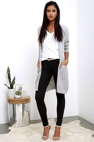 Cómo combinar: cárdigan largo gris, camiseta con cuello en v blanca, pantalones pitillo negros, sandalias de tacón de cuero en beige