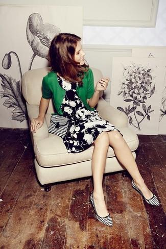 Cómo combinar: cárdigan verde, vestido skater con print de flores en negro y blanco, zapatos de tacón de cuero estampados en negro y blanco, bolso bandolera de lona en negro y blanco