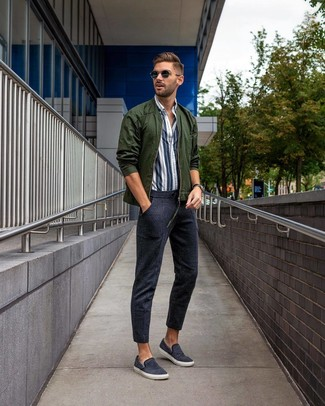 Cómo combinar: cazadora de aviador verde oscuro, camisa de manga larga de rayas verticales en blanco y azul marino, pantalón de chándal azul marino, zapatillas slip-on de lona azul marino