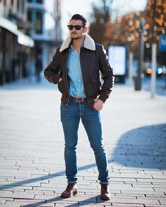 Cómo combinar: cazadora de aviador de cuero en marrón oscuro, camisa vaquera celeste, vaqueros pitillo azules, botas casual de cuero marrónes