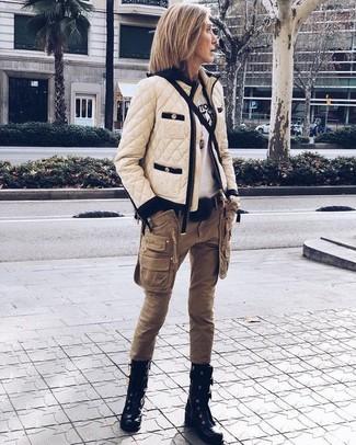 Cómo combinar: cazadora de aviador acolchada en beige, camiseta con cuello circular estampada en blanco y negro, pantalón cargo marrón, botas planas con cordones de cuero negras