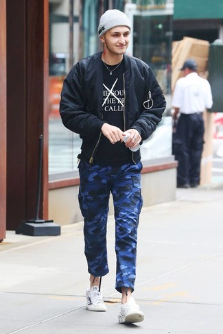 Cómo combinar: cazadora de aviador negra, camiseta con cuello circular estampada en negro y blanco, pantalón cargo de camuflaje azul, tenis de cuero estampados blancos