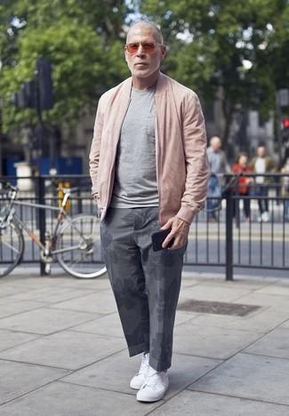 Cómo combinar: cazadora de aviador rosada, camiseta con cuello circular gris, pantalón chino con print de flores gris, tenis de lona blancos