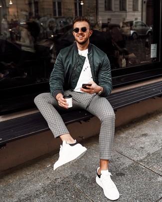 Cómo combinar una cazadora de aviador verde oscuro para hombres de 30 años: Ponte una cazadora de aviador verde oscuro y un pantalón chino de pata de gallo gris para una vestimenta cómoda que queda muy bien junta. Tenis de cuero en blanco y negro son una opción práctica para complementar tu atuendo.