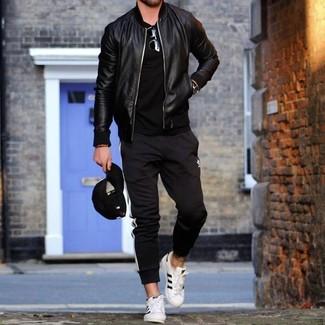 Cómo combinar: cazadora de aviador de cuero negra, camiseta con cuello circular negra, pantalón de chándal de rayas verticales en negro y blanco, tenis de cuero blancos