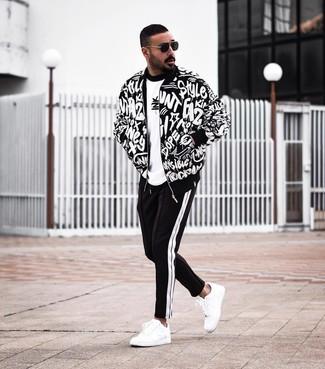 Cómo combinar: cazadora de aviador estampada en negro y blanco, camiseta con cuello circular estampada en blanco y negro, pantalón de chándal en negro y blanco, tenis de cuero blancos