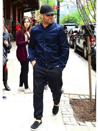 Cómo combinar: cazadora de aviador azul marino, camiseta con cuello circular blanca, pantalón de chándal negro, zapatillas slip-on de lona negras