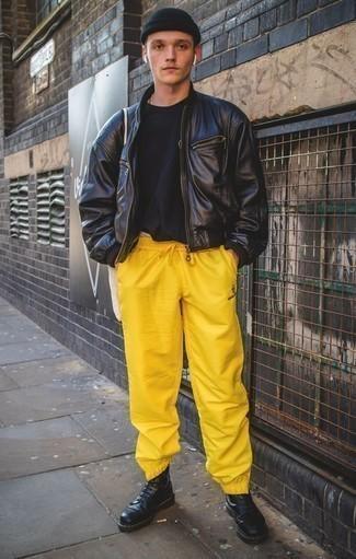 Cómo combinar una camiseta con cuello circular negra: Para un atuendo tan cómodo como tu sillón empareja una camiseta con cuello circular negra junto a un pantalón de chándal amarillo. Activa tu modo fiera sartorial y haz de botas casual de cuero negras tu calzado.