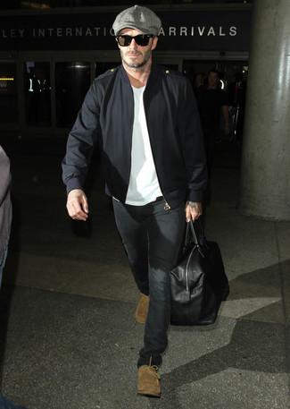 Look de David Beckham: Cazadora de Aviador Negra, Camiseta con Cuello Circular Blanca, Vaqueros Negros, Botas Safari de Ante Marrón Claro