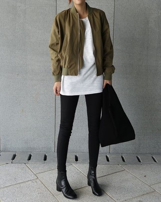 Cómo combinar: cazadora de aviador verde oliva, camiseta con cuello circular blanca, vaqueros pitillo negros, botines chelsea de cuero negros