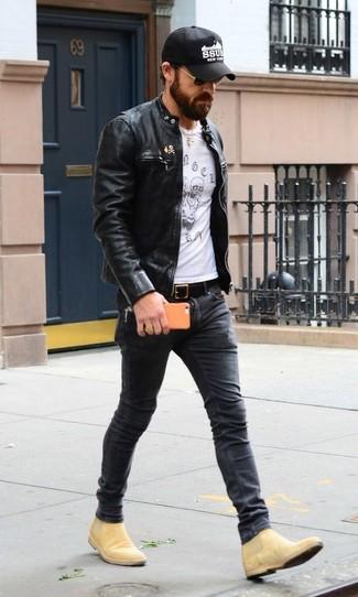 Cómo combinar: cazadora de aviador de cuero negra, camiseta con cuello circular estampada en blanco y negro, vaqueros pitillo en gris oscuro, botines chelsea de ante marrón claro
