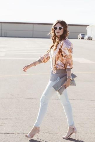 Cómo combinar: cazadora de aviador dorada, camiseta con cuello circular gris, vaqueros pitillo blancos, sandalias de tacón de cuero rosadas