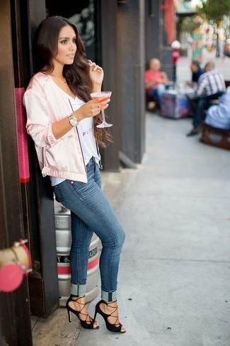 Cómo combinar: cazadora de aviador de satén rosada, camiseta con cuello en v estampada blanca, vaqueros pitillo azules, sandalias de tacón de ante negras