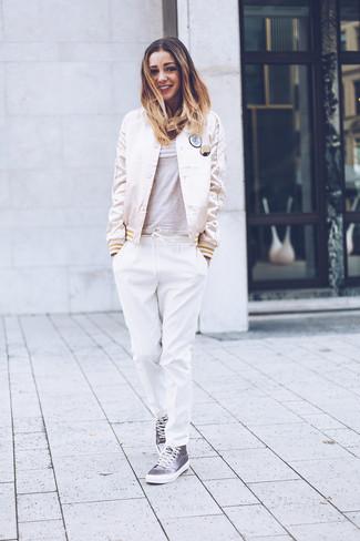 Cómo combinar un pantalón de pinzas blanco: Haz de una cazadora de aviador de satén en beige y un pantalón de pinzas blanco tu atuendo para lidiar sin esfuerzo con lo que sea que te traiga el día. Para el calzado ve por el camino informal con zapatillas altas de lona grises.