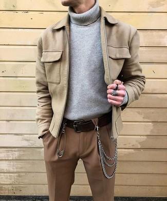 Cómo combinar: cazadora de aviador de ante en beige, jersey de cuello alto de punto gris, pantalón de vestir marrón, correa de cuero en marrón oscuro