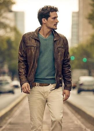 Cómo combinar: cazadora de aviador de cuero en marrón oscuro, jersey de pico verde, vaqueros en beige, correa de cuero marrón