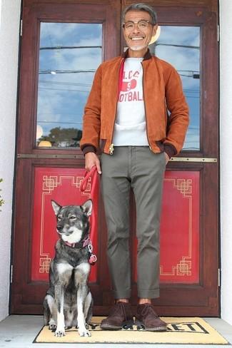 Cómo combinar: cazadora de aviador de ante en tabaco, camiseta con cuello circular estampada en blanco y rojo, pantalón chino gris, botas safari de ante burdeos