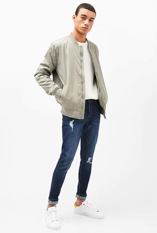 Cómo combinar: cazadora de aviador gris, jersey con cuello circular blanco, vaqueros desgastados azul marino, tenis de cuero blancos