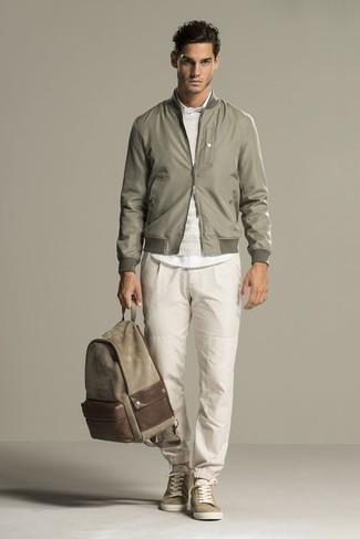 Cómo combinar: cazadora de aviador verde oliva, jersey con cuello circular en beige, camisa de vestir blanca, pantalón de chándal en beige