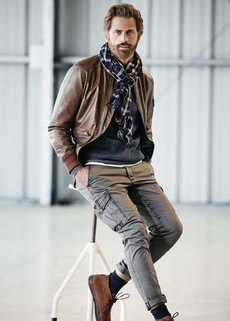 Cómo combinar: cazadora de aviador de cuero marrón, jersey con cuello circular azul marino, pantalón cargo gris, botas safari de ante marrónes