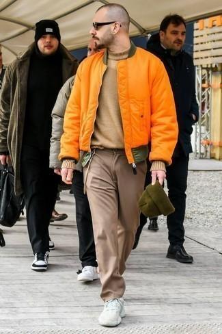 Outfits hombres en clima fresco estilo casuale: Empareja una cazadora de aviador naranja junto a un pantalón chino marrón claro para una vestimenta cómoda que queda muy bien junta. ¿Quieres elegir un zapato informal? Opta por un par de deportivas blancas para el día.