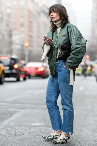 Cómo combinar: cazadora de aviador verde oscuro, jersey de cuello alto de punto en beige, vaqueros azules, zapatos de tacón de pelo de becerro estampados en blanco y negro