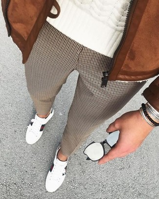 Cómo combinar: cazadora de aviador de ante en tabaco, jersey de ochos blanco, pantalón de vestir de pata de gallo marrón, tenis de cuero blancos