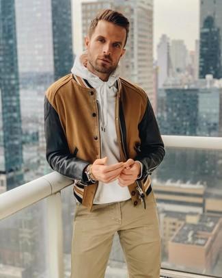 Cómo combinar: cazadora de aviador marrón, sudadera con capucha blanca, pantalón chino marrón claro, reloj de cuero marrón