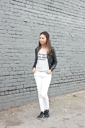 Cómo combinar: cazadora de aviador de cuero negra, camiseta con cuello circular estampada gris, vaqueros blancos, deportivas negras