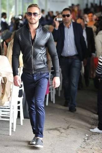 Cómo combinar: cazadora de aviador de cuero acolchada negra, camiseta con cuello en v negra, pantalón chino azul marino, zapatillas slip-on de cuero negras