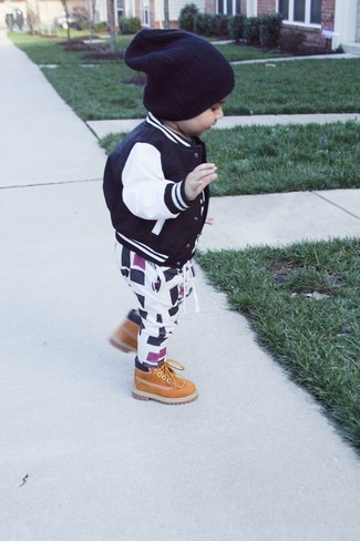 Cómo combinar: cazadora de aviador negra, pantalón de chándal en blanco y negro, botas marrón claro, gorro negro