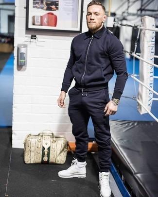 Ponte una cazadora de aviador azul marino de hombres y un pantalón de chándal azul marino para una apariencia fácil de vestir para todos los días. Zapatillas altas de cuero blancas añadirán un nuevo toque a un estilo que de lo contrario es clásico.