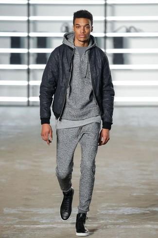 Cómo combinar: cazadora de aviador negra, sudadera con capucha gris, camiseta con cuello circular gris, pantalón de chándal gris