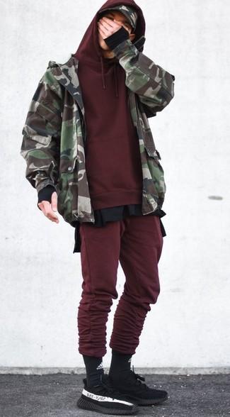 Cómo combinar: cazadora de aviador de camuflaje verde oliva, sudadera con capucha burdeos, camiseta de manga larga negra, pantalón de chándal burdeos
