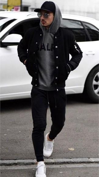 Cómo combinar: cazadora de aviador negra, sudadera con capucha estampada gris, pantalón de chándal negro, tenis de cuero blancos