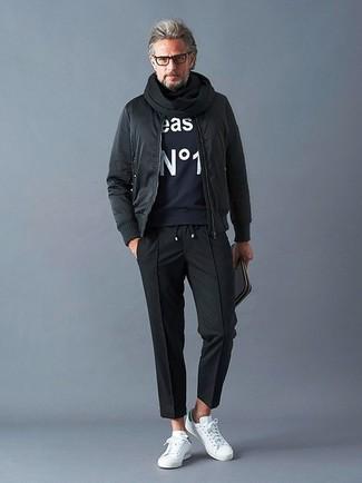 Cómo combinar: cazadora de aviador negra, sudadera estampada azul marino, pantalón chino negro, tenis de cuero blancos