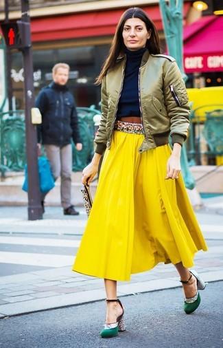 Cómo combinar: cazadora de aviador verde oliva, jersey de cuello alto azul marino, falda midi plisada amarilla, zapatos de tacón de satén verdes