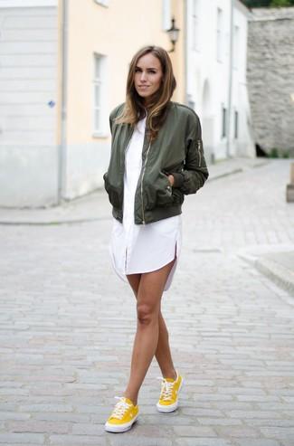 Ponte una cazadora de aviador verde oliva y una vestido camisa blanca para un look diario sin parecer demasiado arreglada. Tenis amarillos son una opción estupenda para complementar tu atuendo.