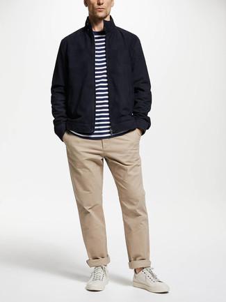 Cómo combinar: cazadora harrington azul marino, camiseta con cuello circular de rayas horizontales en blanco y azul marino, pantalón chino en beige, tenis de cuero blancos