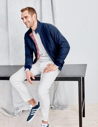 Cómo combinar: cazadora harrington azul marino, camiseta de manga larga gris, pantalón chino blanco, tenis de ante azul marino