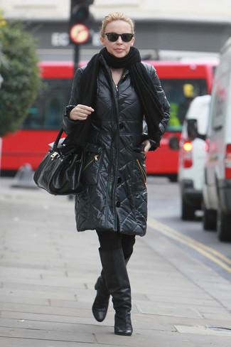 Cómo combinar: chal negro, abrigo de plumón negro, leggings negros, botas de caña alta de cuero negras