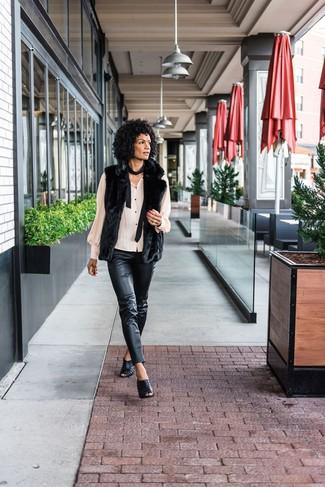 Cómo combinar: chaleco de pelo negro, blusa de botones en beige, pantalones pitillo de cuero negros, chinelas de cuero negras