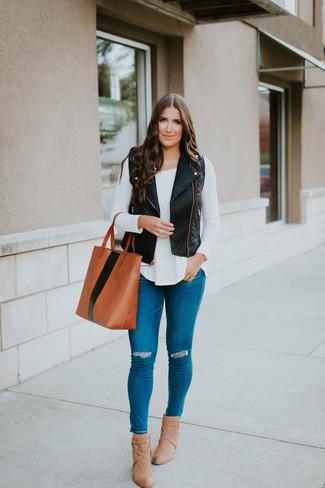 Cómo combinar: chaleco de cuero negro, camiseta de manga larga blanca, vaqueros pitillo desgastados azules, botines de cuero marrón claro