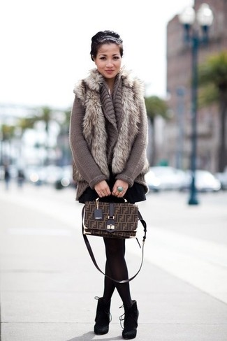 Cómo combinar: chaleco de pelo gris, cárdigan abierto de punto gris, falda skater negra, botines de ante negros