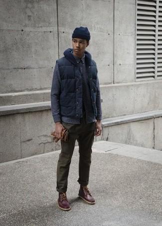 Cómo combinar: chaleco de abrigo azul marino, camisa de manga larga estampada azul marino, pantalón chino verde oliva, botas de trabajo de cuero en marrón oscuro