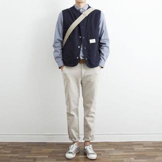 Cómo combinar un pantalón chino en beige: Empareja un chaleco de abrigo azul marino con un pantalón chino en beige para una vestimenta cómoda que queda muy bien junta. ¿Por qué no añadir tenis de lona grises a la combinación para dar una sensación más relajada?