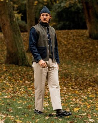 Cómo combinar: chaleco de abrigo de lana en gris oscuro, chaqueta vaquera azul marino, jersey de cuello alto verde oliva, pantalón chino en beige