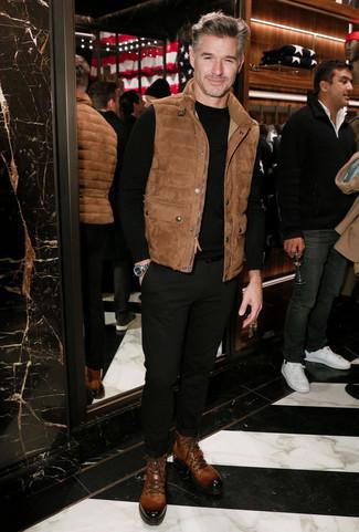Outfits hombres en clima cálido: Usa un chaleco de abrigo de ante marrón y un pantalón chino negro para cualquier sorpresa que haya en el día. Con el calzado, sé más clásico y opta por un par de botas casual de cuero marrónes.