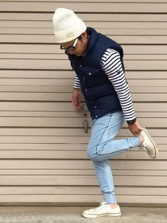 Cómo combinar: chaleco de abrigo acolchado azul marino, jersey con cuello circular de rayas horizontales en blanco y azul marino, vaqueros celestes, tenis blancos
